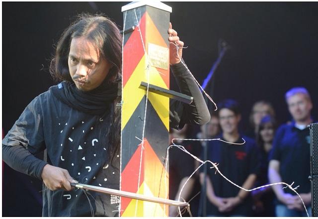 Kurios...Ein indonesischer Künstler macht Musik auf einem Grenzpfosten