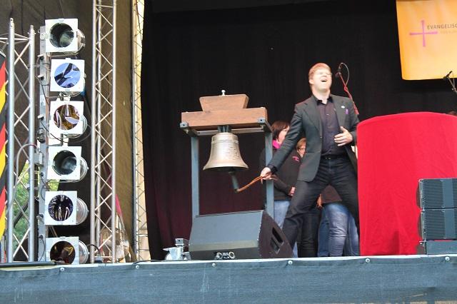 Moderator und Liedermacher Fabian Vogt läutet die Einheitsglocke